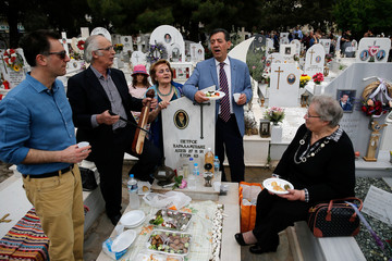 People sing over a grave on Saint Thomas Sunday, when descendants of Greeks who emigrated from the Pontus commemorate their dead ancestors by sharing Easter meal on their graves in Athens