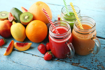 Sweet smoothie in glass jars with fruits on blue wooden table