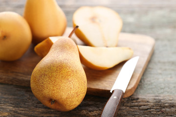 Ripe and sweet pears with knife on cutting board