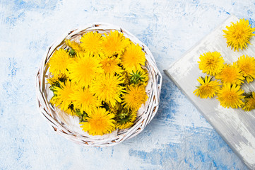 Dandelion flowers in wicker bowl top view