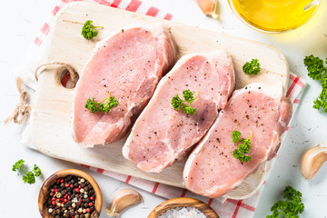 Pork meat steak on white top view.