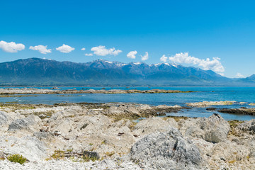 Beautiful New Zealand natural rock sea coast with mountain landscape background