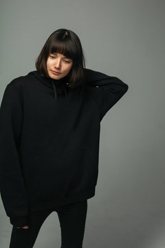 Young woman with black short hair, posing in studio, looking down. dressed in black oversize hoodie, grey background
