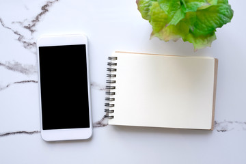 Smartphone with blank screen and blank notebook paper on white marble background, mock up, flat lay