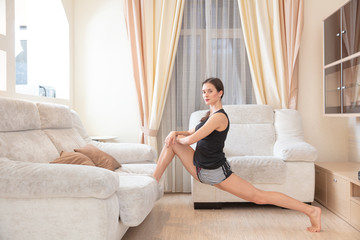 young girl makes exercise lunge legs on sofa