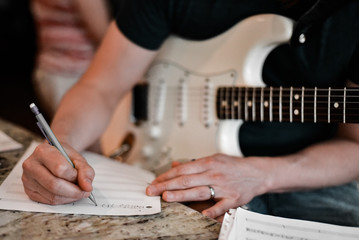 Man with Electric Guitar Writing Music