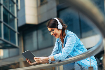 Young woman listens to music via headphones and digital tablet in the city