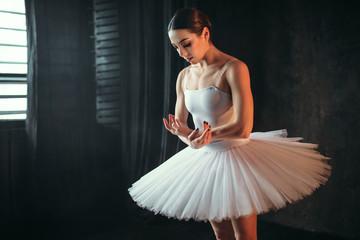 Ballerina dancing in studio against window