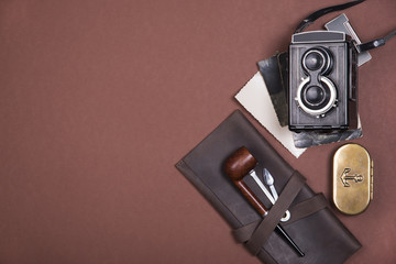 Composition of smoking pipe on a brown leather case, tobacco accessories, old camera and vintage photographs. Top view.