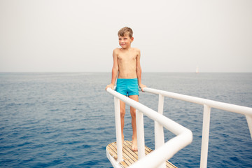 Small boy enjoying summer vacation on sea. Happy boy on yacht cruise. Image with copy space