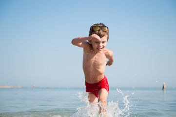 healthy cute happy little kid wearing sunglasses and red shorts running in ocean water with splashes in summer holiday