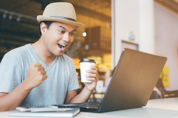 business asian man hand holding paper cup of take away drinking coffee hot sitting working on his computer notebook laptop in a cafe coffee shop. fist hands Show signs of enjoy and gladness happy.