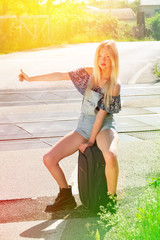 Beautiful blonde  young girl hitchhiking along a road.