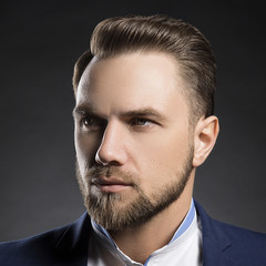 Face of handsome stylish caucasian bearded young man in elegant blue suit and white shirt with perfect hair style