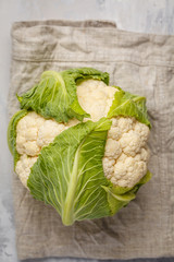 Ripe whole raw cauliflower on a light background on a napkin, top view. Healthy vegan food concept.