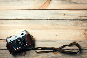 Old vintage film photo camera with brown leather strap on grunge wooden table. Photographe concept background