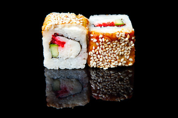 Traditional fresh japanese sushi rolls on a black background with reflection.