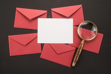 Envelopes and magnifier on black background
