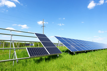 Solar panel installation on blue sky background. Green grass and cloudy sky. Alternative energy concept