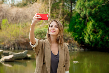 Redhead girl making selfie with mobile phone in a park in spring time