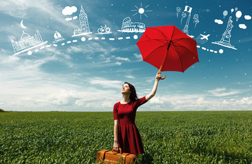 portrait of young beautiful woman with suitcase and red umbrella in the field and travel map