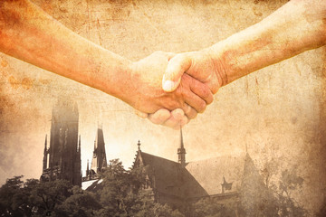 handshake of two conflict people with Church on background