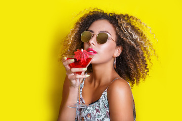 Beautiful afro american woman with pink cocktail at a party in summer.