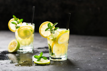 Lemon fruit lime slices caipirinha from Brazil, lemonade mint ice cubes in cold glasses on dark background, alcoholic mojito cockail ice tea green mint leaves, brown sugar spoon, copy space