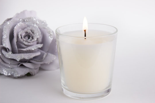 Candle in glass on white background with a rose, product mock-up
