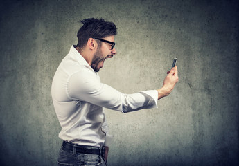 angry man holding smartphone and shouting in anger