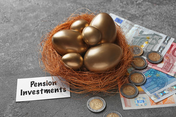 Golden eggs in nest, money and sign PENSION INVESTMENTS on grey background