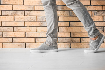 Man in casual shoes near brick wall