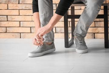 Man tying shoelaces indoors