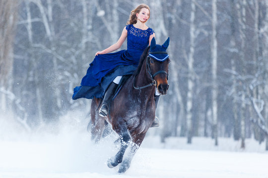 Young girl in blue dress galloping horseback on winter field. Romantic or historical equestrian background with copy space