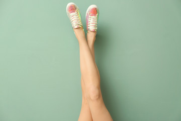 Legs of young woman in stylish casual shoes on color background