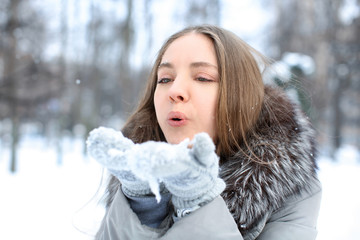 Beautiful young girl playing with snow in park on winter vacation