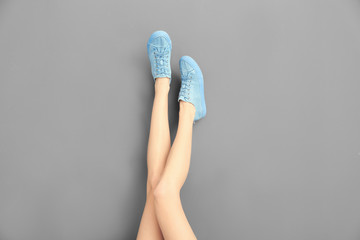 Legs of beautiful woman in stylish shoes on color background