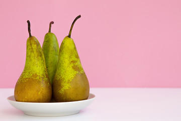 three ripe long pears on a saucer on a creative pink background