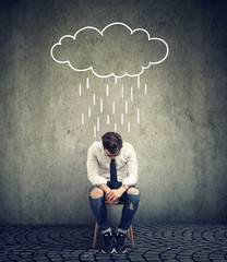 Sad business man sitting on a chair looking down with a rain cloud above him