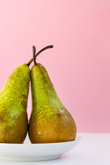 two ripe wet pears on a saucer on a creative pink background