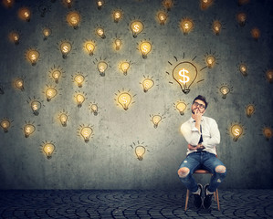 thinking freelancer man sitting on chair looking up at many dollar idea light bulbs above head