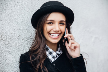 Smiling urban girl uses smart phone with smile on her face.Portrait of fashionable gir wearing a rock black style having fun outdoors