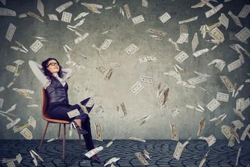 Successful woman sitting under money rain