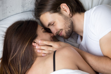 Happy affectionate young couple lying in bed face to face, smiling lovers enjoying intimacy and pleasant morning together, man tenderly touching woman, love and sensuality concept, close up top view