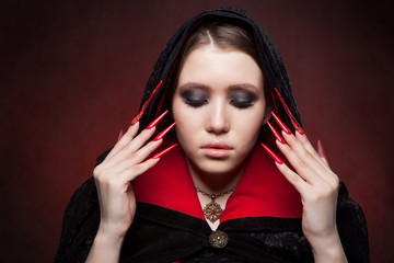 Vintage style portrait of young beautiful vampire woman with gothic Halloween makeup. Manicured red stilettos nails.