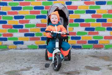 Happy boy in bright suit is riding children's bicycle wheelchair against background of multicolored brick wall. Romantic lighting with sunlight reflections. Lens flare effect without post prodaction