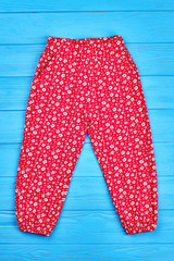 Baby girl summer colored leggings. Vertical image of female infant red pants. Fashionable casual trousers for little girls.