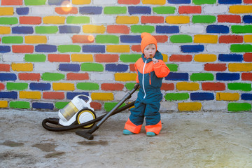 Happy boy in bright suit with a vacuum cleaner and candy against background of multi-colored brick wall. Romantic lighting with reflection of sunlight. Effect of lens flares without post-production
