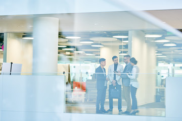 Multi-ethnic team of white collar workers discussing details of start-up project while standing at modern office lobby, view through glass wall
