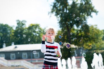 Little blondy girl playing with soap bubbles in summer park